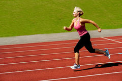Athletic woman running on track Royalty Free Stock Photos