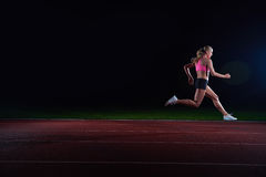 Athletic woman running on track Royalty Free Stock Image