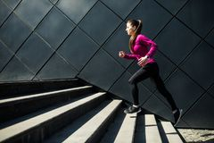 Athletic woman running up stairs during cardio. interval training royalty free stock image