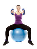 Athletic woman sitting on a ball and working with dumbbells Stock Photo