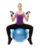 Athletic woman sitting on a ball and working with dumbbells Royalty Free Stock Photo