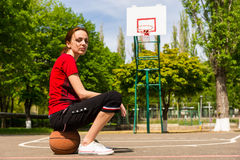 Athletic Woman Sitting on Basketball on Court Royalty Free Stock Photos