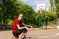 Athletic Woman Sitting on Basketball on Court Royalty Free Stock Images