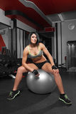 Athletic woman sitting on a gym ball Stock Image