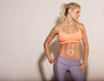 Athletic Woman with Sixpack Abs. Confident athletic woman with sixpack abs posing royalty free stock photo
