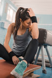 Athletic woman in sportswear sitting on mat in sports hall Royalty Free Stock Photography