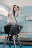 Athletic woman in sportswear sitting on pommel horse in gym Stock Photos