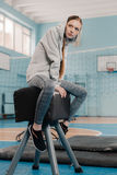 Athletic woman in sportswear sitting on pommel horse in sports hall Stock Photography