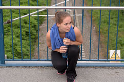 Athletic Woman Squatting at the Bridge with Water Stock Photos