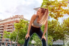 An athletic woman standing with her hands on her knees. An athletic woman in a grey top standing with her hands on her knees in the park with modern buildings in royalty free stock images