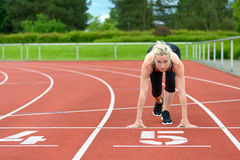 Athletic woman in the starter position on a track. Athletic woman crouched down in the starter position on a race track at a sporting venue looking up at the Royalty Free Stock Image