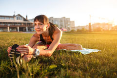 Athletic woman stretching her hamstring, legs exercise training fitness before workout outside with headphones Royalty Free Stock Images