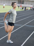 Athletic woman stretching leg muscles Royalty Free Stock Photo