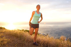 Athletic woman stretching outdoors by sunset Royalty Free Stock Photography