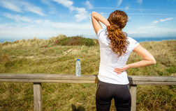 Athletic woman touching neck and back muscles by stock photography
