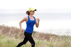Athletic woman trail running by sea in baseball cap Royalty Free Stock Photography
