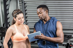 Athletic woman and trainer looking at tablet Stock Photos