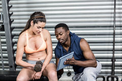 Athletic woman and trainer looking at tablet Royalty Free Stock Photography