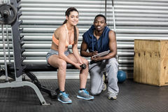 Athletic woman and trainer smiling to camera. Athletic women and trainer smiling to camera at crossfit gym Royalty Free Stock Photos