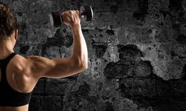 Athletic woman training biceps on grunge background stock photography