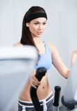 Athletic woman training in gym. Young athletic woman training on training apparatus in gym Stock Photography