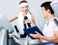 Athletic woman training on gym. Young athletic women training on gym training in gym with coach writing down the results Stock Images