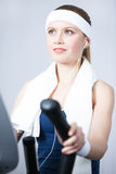 Athletic woman training on gym equipment in gym Stock Images