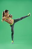 Athletic woman training her high kick in studio on green backgro. She is a fighter. Vertical shot of a woman in sportswear practicing her kickboxing technique on Royalty Free Stock Photography