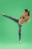 Athletic woman training her high kick in studio on green backgro. Kickboxing woman. Vertical shot of a female fighter in sportswear performing high kick on green Royalty Free Stock Photos