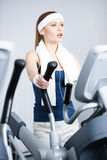 Athletic woman training on simulators in gym Stock Images