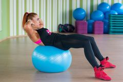Athletic woman trains press on the fitness ball in sport gym. Royalty Free Stock Image