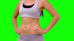 Athletic woman turning to camera against green screen. In slow motion stock video