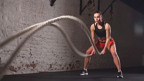 Athletic woman using training ropes for exercise at gym.