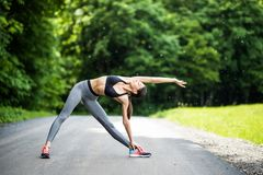 Athletic woman warming up before a workout standing facing the e royalty free stock photos