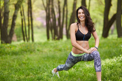 Athletic woman warming up. Young female athlete stretching Stock Photos