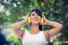 Athletic woman wearing yellow headphones and enjoying music Stock Photos