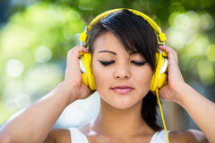 Athletic woman wearing yellow headphones and enjoying music with eyes closed Royalty Free Stock Photos