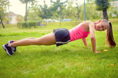 Athletic woman working happy in park with push ups, abs Royalty Free Stock Image