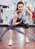 Athletic woman working her biceps with dumbbells at the gym Stock Photos
