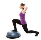 Athletic woman working her legs on a bosu ball. Full length studio shot of athletic woman working out her legs on a bosu bal, isolated over white background Stock Photography