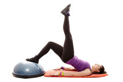 Athletic woman working her legs and bottom on a bosu ball. Studio shot of young athletic woman lying on the floor working out her legs and bottom on a bosu ball Royalty Free Stock Photography