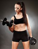 Athletic woman working out with dumbbells Royalty Free Stock Photo