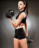 Athletic woman working out with dumbbells Stock Images