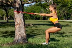Athletic woman workout squats with resistance band outdoors. Fitness girl doing exercise for back and legs at the park