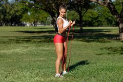 Free Athletic Woman Workout With Resistance Band Outdoors. Fitness Girl Doing Exercise For Biceps At The Park Royalty Free Stock Image - 165473986