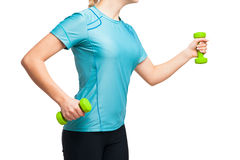 Athletic woman works out with green dumbbells Stock Photo