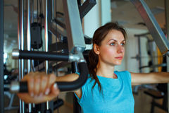 Athletic woman works out on training apparatus in gym. Athletic woman works out on training apparatus in fitness center Stock Images