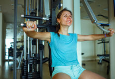 Athletic woman works out on training apparatus in gym. Athletic woman works out on training apparatus in fitness center Royalty Free Stock Photography