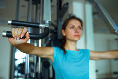 Athletic woman works out on training apparatus in gym. Athletic woman works out on training apparatus in fitness center Royalty Free Stock Photo