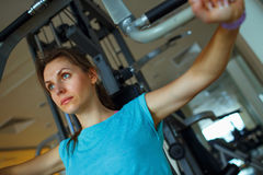 Athletic woman works out on training apparatus in gym. Athletic woman works out on training apparatus in fitness center Stock Photography